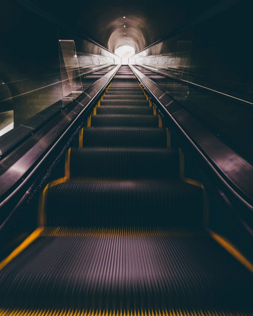 An escalator heading towards the light
