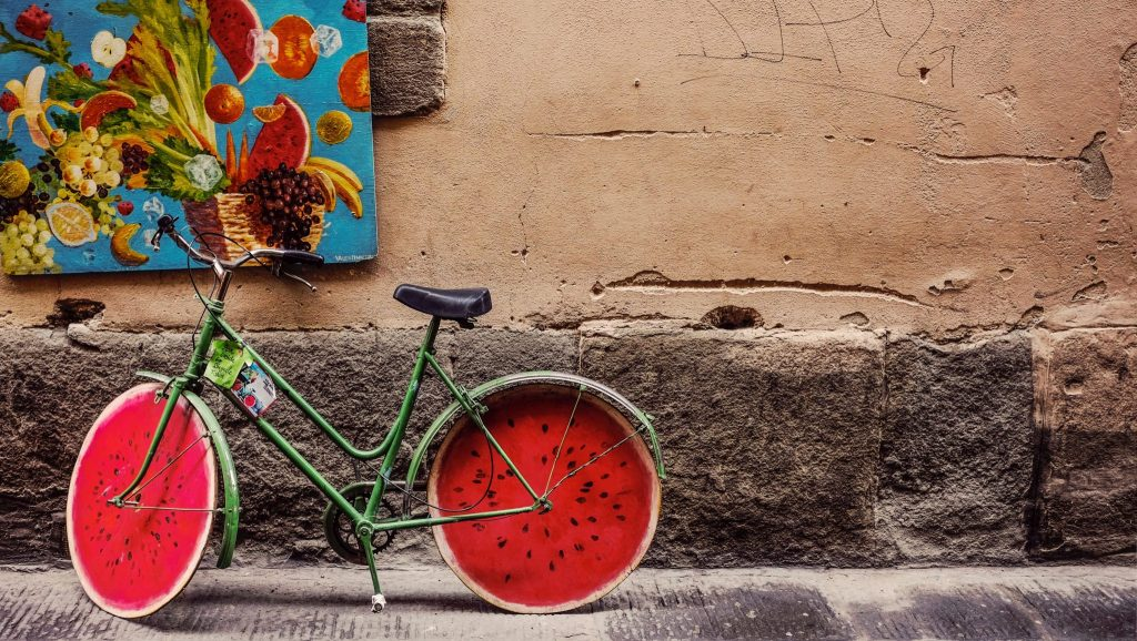 An eye-catching bicycle parked on the side of a building