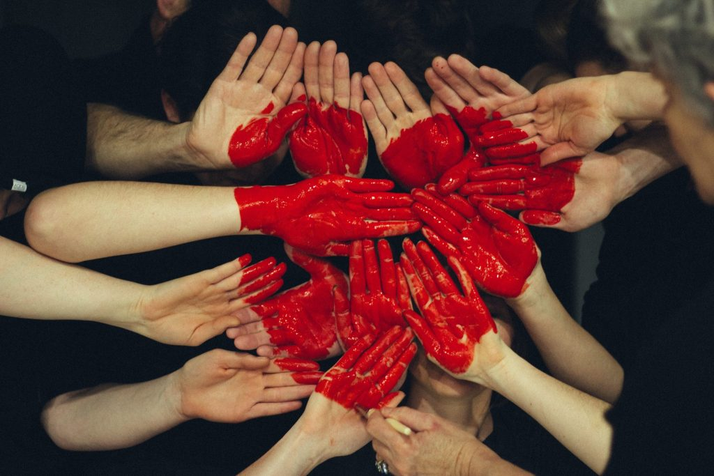 Hands painted in a red heart to represent social management